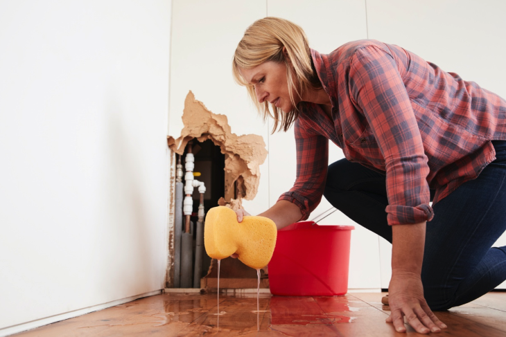 woman mopping up water burst pipe Water Damage